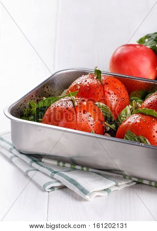 Whole tomatoes with leek garlic balsamic vinegar olive oil and herbs on a baking tray. Vegetables ready for roasting in the oven. Copy space.