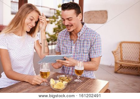 Goodlooking Young Couple Looking At Tablet