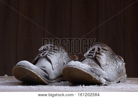 Frozen brown suede shoes with brown laces on the background of dark natural wood.