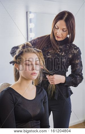 Hairstylist straightening the long brown hair of a female client using a heated hair straightener