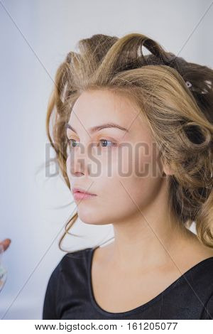 Makeup artist applying liquid tonal foundation on the face of the woman in white make up room. Beauty and fashion concept