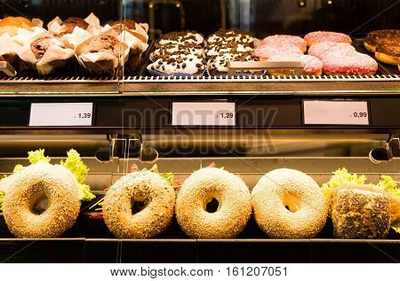 Bright shot of bagels donuts and sandwiches in a bakery or shop glass counter. Shiny showcase of baked fastfood with prices