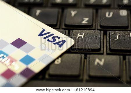 PRAGUE, CZECH REPUBLIC - DECEMBER 12, 2016: VISA payment card put on black keyboard. VISA provides multinational cashless and contactless payments worldwide.