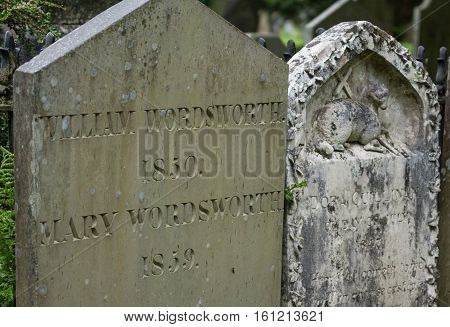 Grasmere England - May 30 2012: In the cemetery of the Saint Oswald Church stands the gray old tombstone of the poet William Wordsworth and his wife Mary Hutchinson. Other tombstone with Agnus Dei. Green foliage.