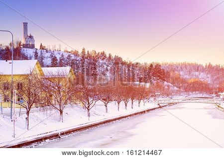 View of small swedish european town Soderhamn with frozen river at sunrise, winter seasonal background