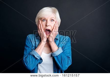 How can it be. DElighted emotional elderly woman holdign her hands on the cheeks and looking at you while expressing wonder