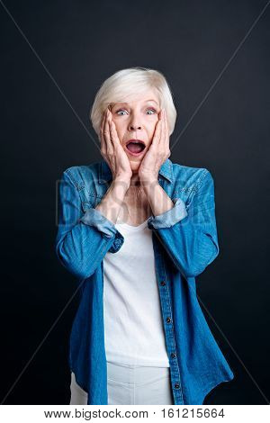 Wow. Astonished elderly woman holding her hands on the fce and lookign at you while being surprised