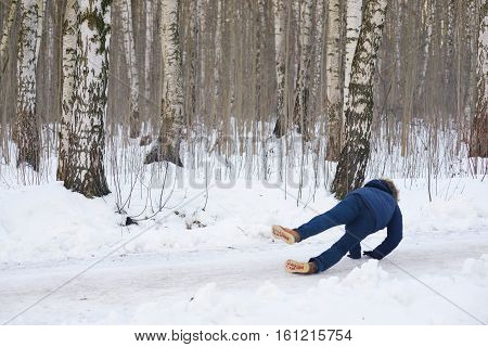 Young stylishly dressed man while walking through a birch forest slipped and fell on a slippery road.