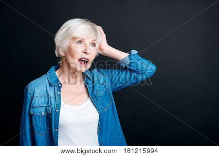 Good idea. Pleasant elderly woman lookign aside and having an idea while standing isolated on black background