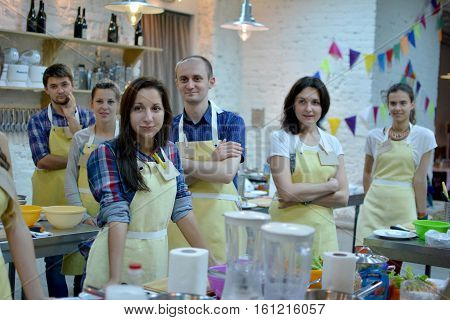 KYIV, UKRAINE - December 13, 2014: Happy group of friends with male chef cook cooking and talking in kitchen. Cooking class.