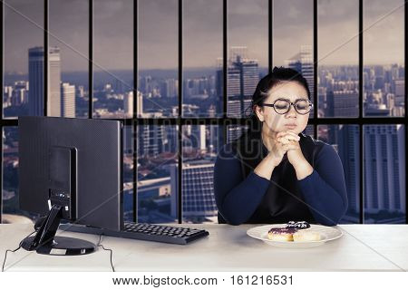 Portrait of an overweight businesswoman working with computer while trying to diet and expressing hesitation
