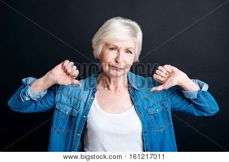 I dont like it. Pleasant aged woman showign disapproval and lookign at you while standing on black background