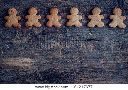 Christmas gingerbread men cookies on old wooden background with space for text. Merry Christmas and Happy New Year. Xmas baking concept. Top view. Copy space.