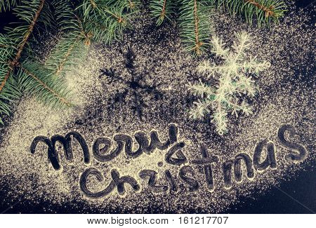Christmas fir tree and snowflakes on chalkboard background. Merry Christmas and Happy New Year. Xmas time background. Winter holidays. Christmas concept. Top view.