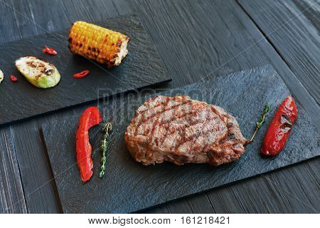 Grilled beef steak cooked on barbecue, closeup on dark wooden table background. Fresh juicy roasted red meat on black stone board, with corn, pepper and rosemary. Restaurant food, delicious dish