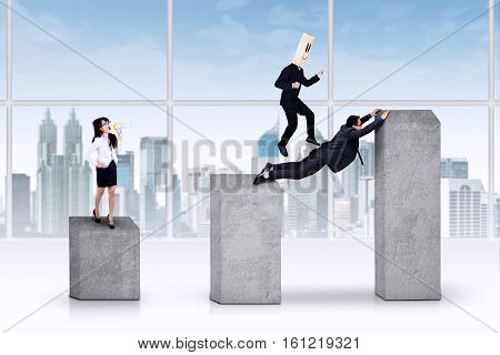 Young asian manager yelling to her team on financial graph in the office