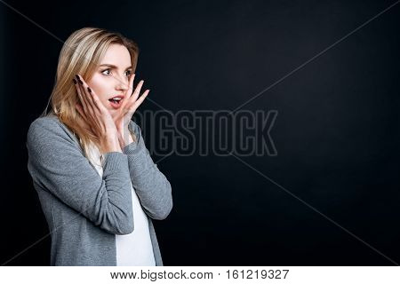 Contraversial emotions. Emotional young woman holding her hands on the face and looking aside while expressing wonder