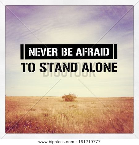 Never be afraid to stand alone. Isolated bush in prairie field with motivational quote.  Inspirational quote on prairie field landscape.  Instagram effects