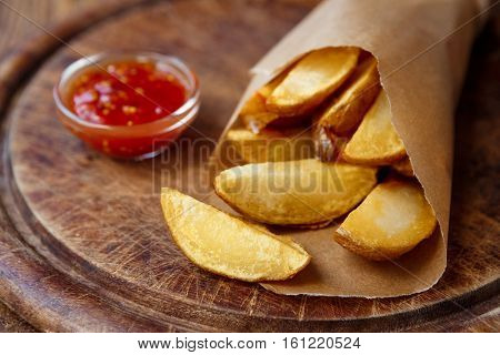 Potato wedges wrapped in brown craft paper. Fast food take away on rustic wood. Fried slices with tomato sauce. Selective focus, shallow DOF
