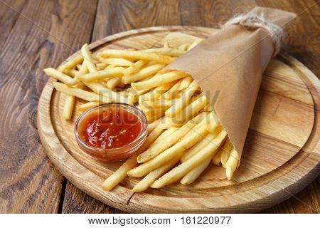 French fries wrapped in brown craft paper. Fast food take away on rustic wood. Fried potato chips with tomato sauce.