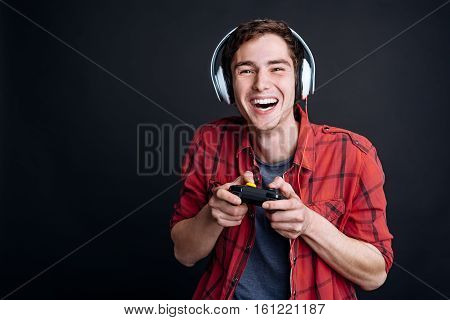 True emotions. Delighted smiling young man holding game console and playing video games while enjoying his free time