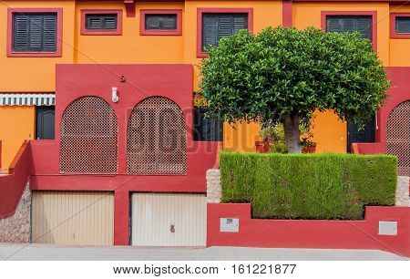 Fragment of colorful spanish residental house with green fence
