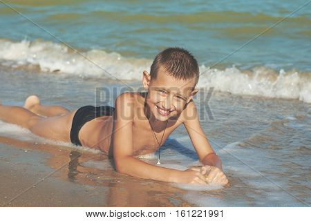 Happy Children - little boy having fun on the beach. Positive human emotions.