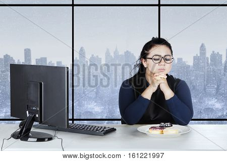 Overweight businesswoman sits in the workplace and looks confused to eat donuts with computer on the desk