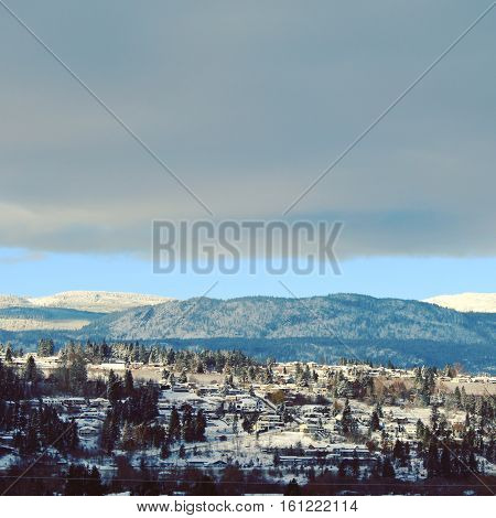 Winter landscape.  Sunshine on bright white snow covered forest hills and mountains with green trees and houses on hills.  Grey dark clouds and blue sky background over mountains in background.