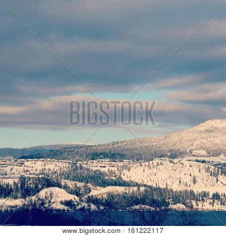 Winter landscape with lake and trees in foreground.  Sunshine on bright white snow covered forest hills.  Grey, white and pink colored clouds and blue sky background over mountains.