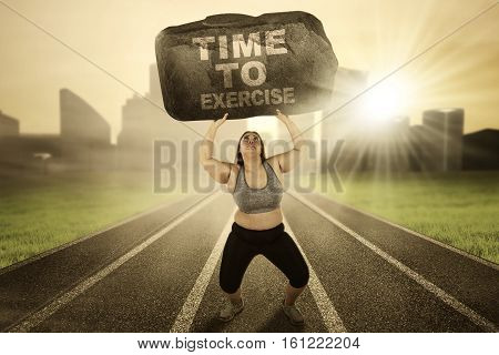 Image of obese female lifting a big stone with text of time to exercise while running on the track