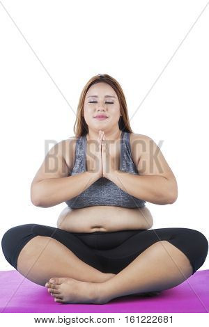 Image of overweight young woman sitting on a purple mattress while practicing yoga isolated on white background