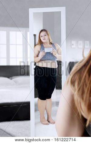 Image of overweight woman standing in front of the mirror while taking selfie photos with smartphone in the bedroom