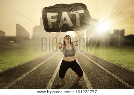 Picture of overweight woman lifting a boulder with fat word while running on the track