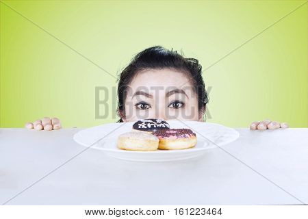 Picture of young female is peeping donuts on the table shot with green background