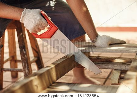 Caucasian man working cutting plank with handsaw. Carpentry construction.