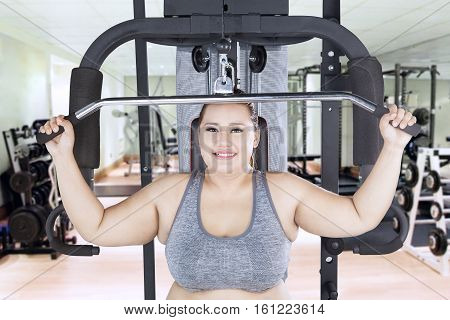 Portrait of overweight woman exercising and flexing muscles with a cable machine in the fitness center