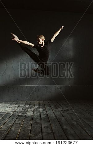 Performing split in the air. Skillful proficient young dancer performing in the dark lighted room and having a stretching session while showing his flexibility in the air