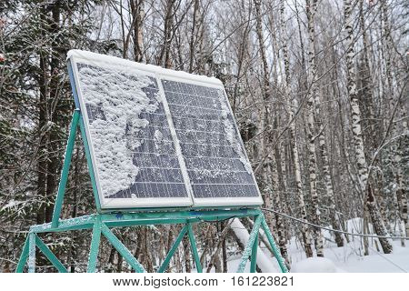 Solar panel plant under the snow in winter forest.