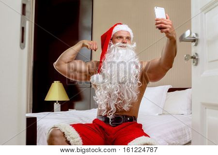 Strong Santa Claus is making selfie, looking at camera and smiling