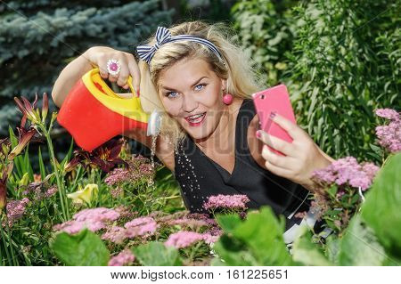 Woman making selfie when gardening. Housewife between flowers while watering cans - Smartphone photography