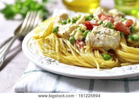 Codfish In A Cream Sauce With Vegetables Garnished With Spaghetti.