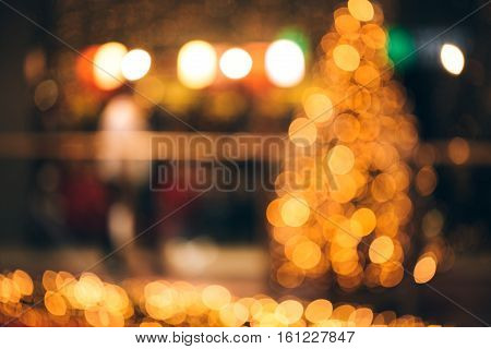 Blurred festive background made with christmas tree and lights. New year backdrop.