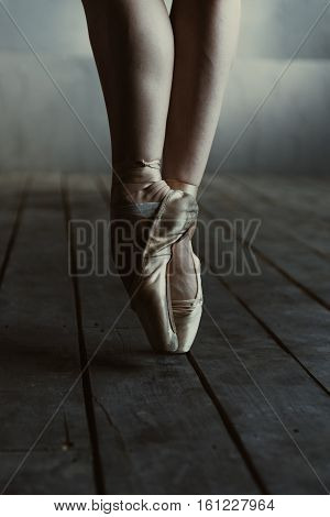 Graceful ballet dancer legs . Concentrated proficient skilled ballet dancer showing her legs while standing isolated on the tiptoes in pointes on the black colored floor and performing