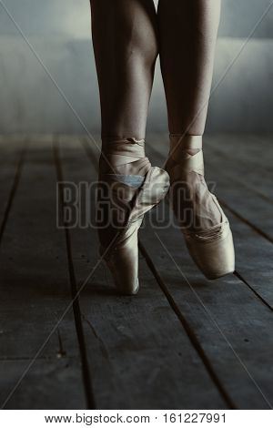 Concentration in details. Proficient concentrated skilled ballet dancer demonstrating her legs while standing isolated on the tiptoes in pointes on the black colored floor and performing
