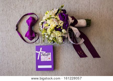 bridal bouquet of white and blue flowers rings purple butterfly and invitation-cards lie on a light background preparations for the wedding the groom's fees dress wedding attributes