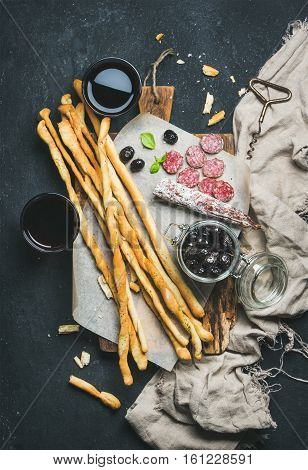Wine and appetizers set. Italian Grissini bread sticks, dry cured pork meat sausage, black olives on rustic wooden serving board and red wine in glasses over dark stone background, top view