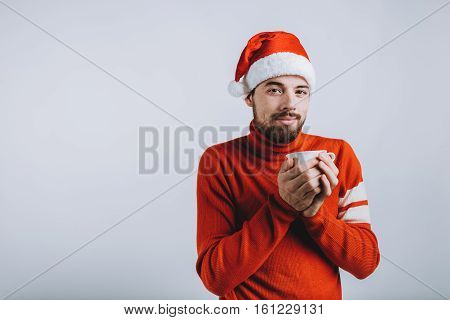 Winter concept - Christmas holiday. Happy man in Santa's hat and red sweater is looking at camera and holding cup with hot tea. Isolated on white background