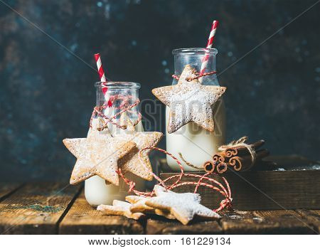 Bottles with milk for Santa, Christmas festive gingerbread star shaped cookies with decoration rope, spices on wooden rustic table, dark blue background, copy space, horizontal composition
