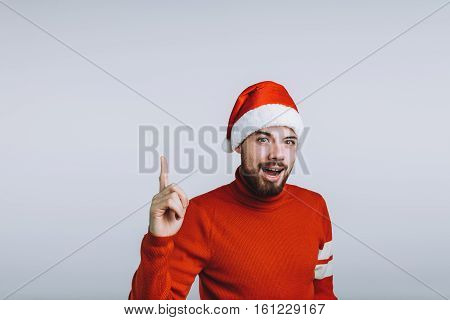 Winter concept - Christmas holiday. Happy young man is pointing up with his finger. He is wearing Santa's hat and red sweater. Isolated on white background